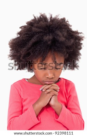 Portrait of a girl praying against a white background - stock photo