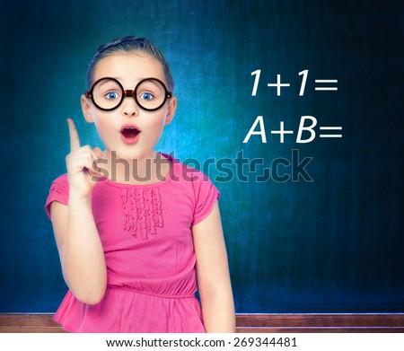 portrait of a girl schoolgirl costs about blackboard, school, class - stock photo