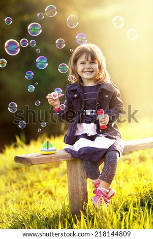 Portrait of a girl sitting on a wooden bench blows bubbles in th - stock photo