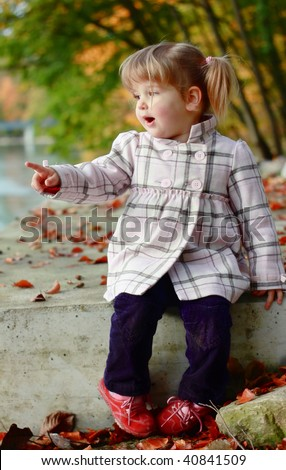 Portrait of a girl sitting on fall leaves - stock photo