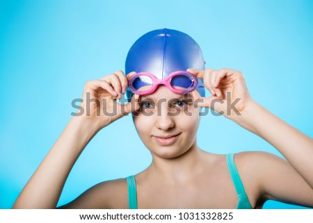 Portrait of a girl sportswoman in a bathing cap and glasses. The girl wears diving goggles. A bright blue background. Horizontal stock photo