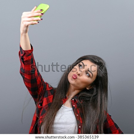 Portrait of a girl taking selfie with cellphone against gray background - stock photo