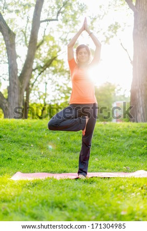 Portrait of a girl taking yoga poses at sunset - stock photo