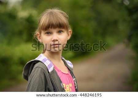portrait of a girl teenager with blonde hair in the background of a rural road