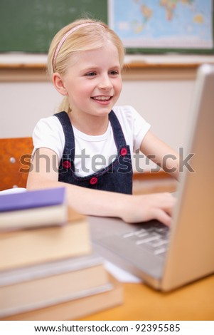 Portrait of a girl using a laptop in a classroom