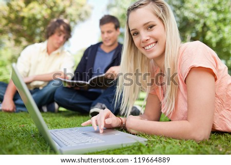 Portrait of a girl using a laptop while lying in a park with friends in background - stock photo