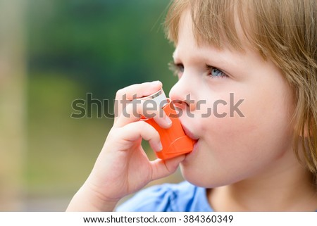 Portrait of a girl using asthma inhaler outdoors - stock photo