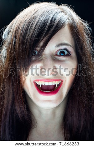 Portrait of a girl vampire on a black background - stock photo