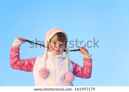 portrait of a girl walking around outdoors in the winter, keeps herself pigtails - stock photo