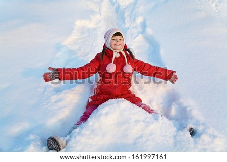 portrait of a girl walking around outdoors in the winter, lying in the snow - stock photo