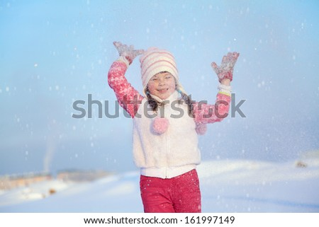 portrait of a girl walking around outdoors in the winter, playing with snow