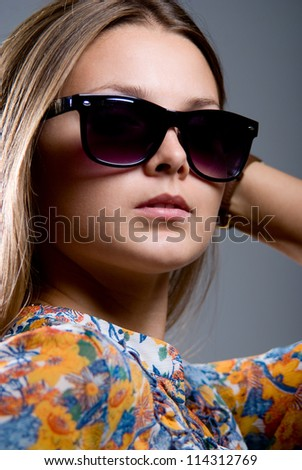 Portrait of a girl wearing sunglasses on a gray background - stock photo