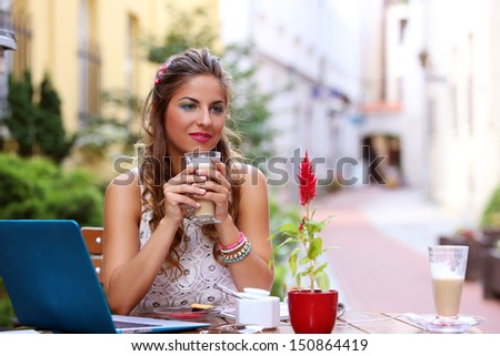 Portrait of a girl who is sitting at a cafe with her laptop and drinking coffee
