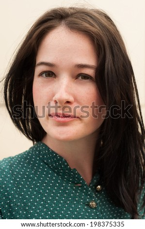 Portrait of a girl with a natural look, posing outdoor and looking into the camera. - stock photo