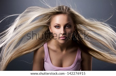 portrait of a girl with blond long waving hair on gray background