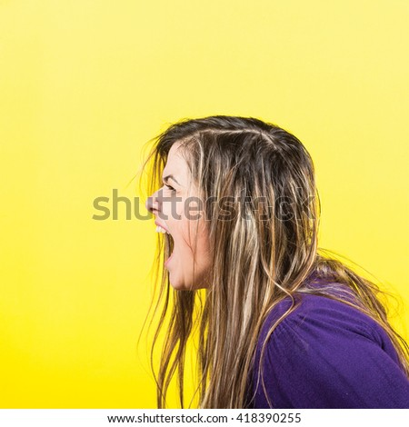 Portrait of a girl with exited yelling face against yellow background - stock photo