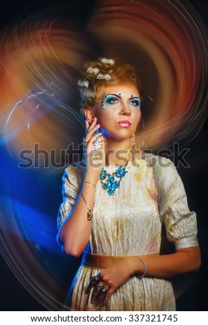 Portrait of a girl with face art, jewelry, and hairstyle. Shot with mixed light. The concept of high fashion. - stock photo