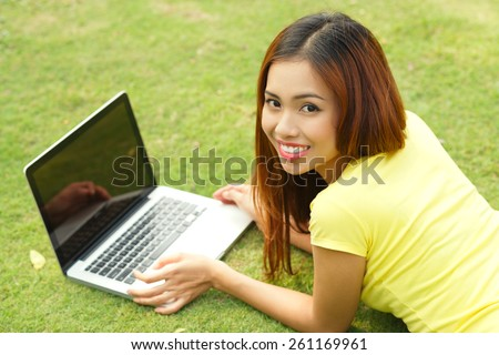 Portrait of a girl with laptop lying on lawn