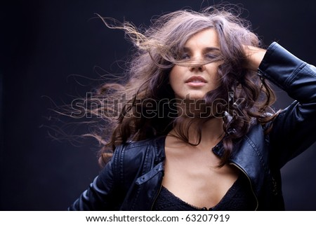 Portrait of a girl with streaming hair against black background - stock photo