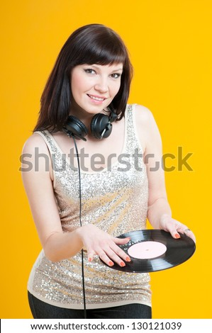 Portrait of a glamorous female DJ posing with a vinyl record - stock photo