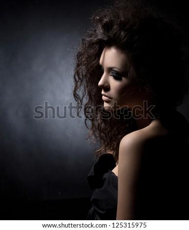 portrait of a glamorous girl in black  dress on dark background - stock photo