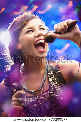 Portrait of a glamorous girl with mike singing song - stock photo