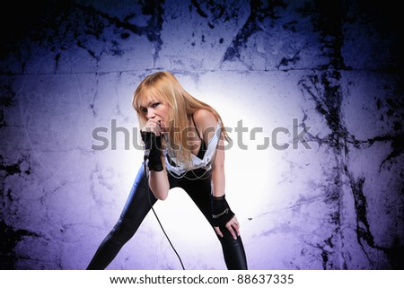 Portrait of a glamorous singer girl holding a mike and singing - stock photo