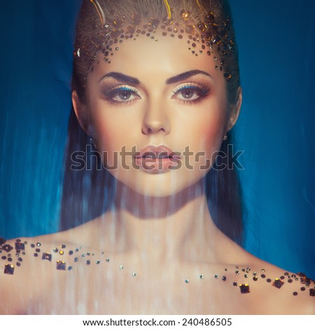 Portrait of a glamorous very beautiful girl brunette with sequins on the face in the Studio - stock photo