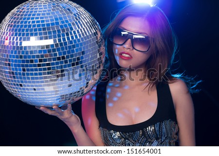 Portrait of a glamorous young lady with a danceball in hands against a black background - stock photo