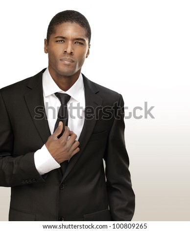 Portrait of a good looking handsome young businessman in black suit with tie against bright background with copy space - stock photo