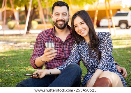 Portrait of a good looking Hispanic young couple having fun with their smartphones and smiling - stock photo
