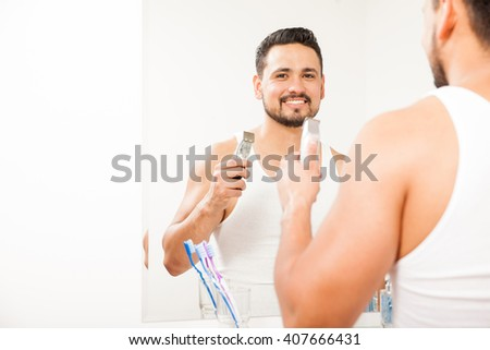 Portrait of a good looking Hispanic young man holding an electric razor and shaving his beard in the bathroom - stock photo
