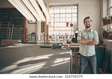 Portrait of a good looking male designer standing in his workshop studio with his arms folded and smiling confidently at the camera - stock photo