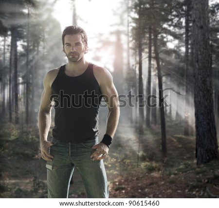 Portrait of a good looking male model in dramatic forest with rays of light behind - stock photo