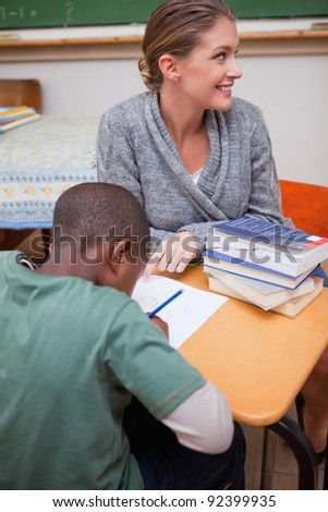 Portrait of a good looking teacher explaining something to a pupil in a classroom - stock photo