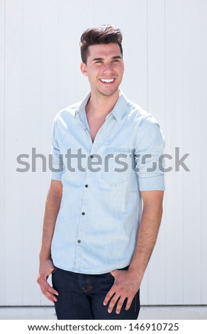 Portrait of a good looking young man smiling outdoors against white background