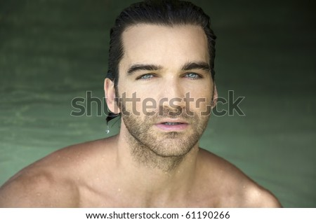 Portrait of a good looking young man with sparkling eyes against background of green water - stock photo