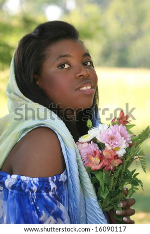Portrait of a gorgeous african-American young woman with flowers, in a summer-time, green park, outdoor setting with a bunch of flowers and a head scarf