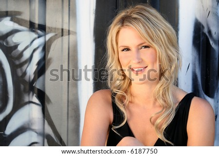 Portrait of a gorgeous blond young woman against a wall of graffiti