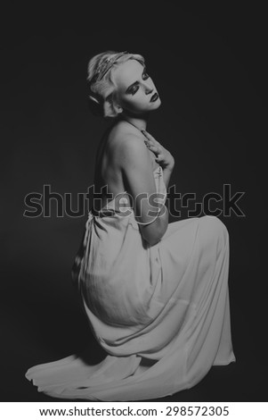Portrait of a gorgeous blonde in a low key. The mystery, sadness, insecurity, human emotions. The girl in the style of the 20s. - stock photo