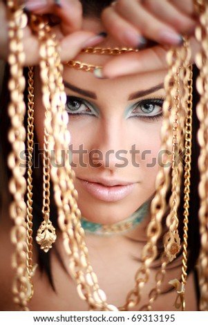 Portrait of a gorgeous brunette holding golden chains in her arms - stock photo