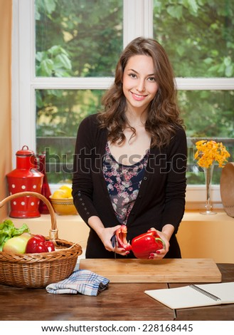 Portrait of a gorgeous brunette preparing healthy meal in the kitchen.