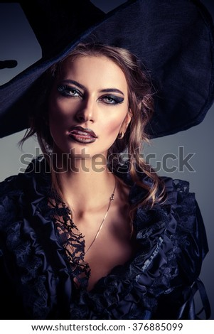 Portrait of a gorgeous brunette witch in black dress and a hat over black background. Halloween.  - stock photo