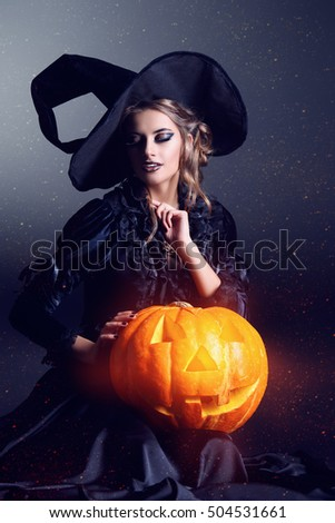 Portrait of a gorgeous brunette witch in black dress and a hat sitting with pumpkin over black background. Halloween.