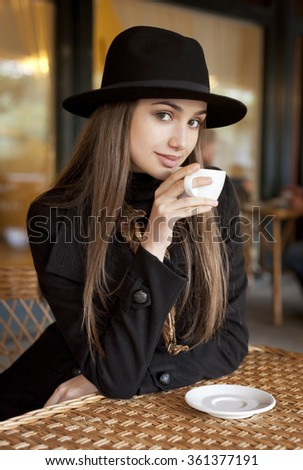 Portrait of a gorgeous brunette woman having coffee.