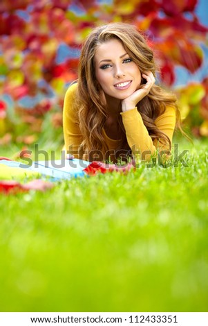 Portrait of a gorgeous brunette woman reading a book in the autumn park. - stock photo