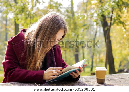 Portrait of a gorgeous brunette woman reading a book in the autumn park.