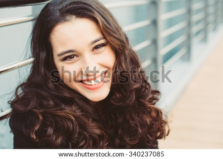 Portrait of a gorgeous brunette woman with wavy hair and beautiful smile - stock photo