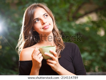 Portrait of a gorgeous cool young brunette woman holding green cup. - stock photo