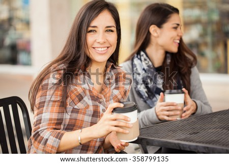 Portrait of a gorgeous Hispanic young woman hanging out with her friends and enjoying a cup of coffee - stock photo